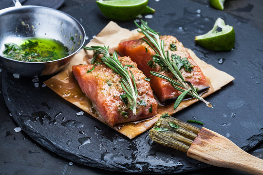 Slices of raw salmon smeared with spices and olive oil shale on a plate close-up. Preparation of fish. Salmon steak.