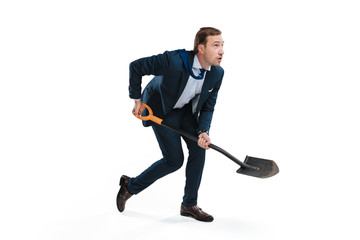 young businessman in formal wear digging with shovel and looking away isolated on white
