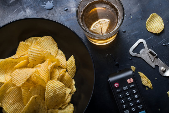 Plate of chips, a glass of beer with lemon, TV remote control, opener closeup on dark metal table. View from above. Free time. Relaxation at tv.