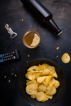 Plate of chips, remote control TV, beer, bottle opener top view of a dark metal table.