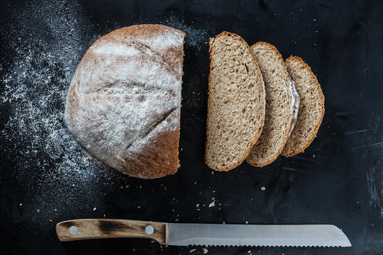 Bread and a knife lying on a black metal table sprinkled with flour