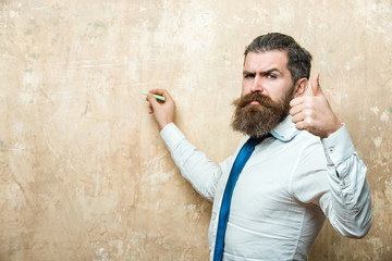 hipster man with beard on serious face write with chalk