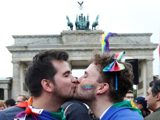 A couple is seen kissing as people celebrate Germany's parliament legalising the same-sex marriage in front of the Brandenburg Gate in Berlin