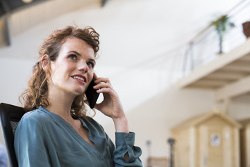 Young woman on the phone in office