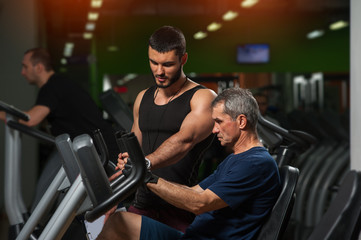 Senior man working with personal trainer in gym