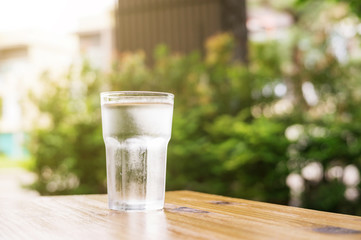 a glass of water on a wooden table.