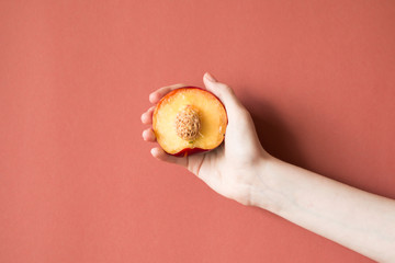 hand with a fresh juicy peach on a red background