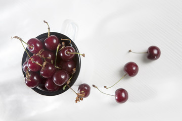 the Uzbek ripe cherry in an enameled cup on a white wooden table. Copy space