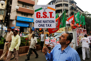 A supporter of India's ruling Bharatiya Janata Party holds a placard during a rally to support implementation of GST in Mumbai