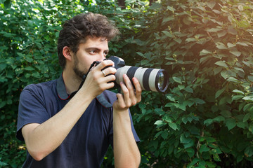 A portrait photographer who takes the photo. In background of green bushes.
