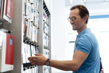 Smiling man looking at phone covers at store