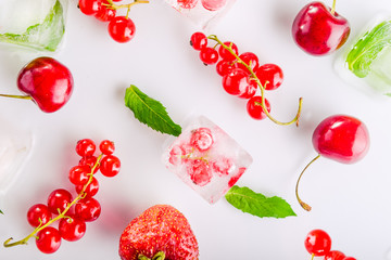 Top view ice cubes with fresh berries among not frozen cherry, strawberry and mint leafs on the white background. Selective focus