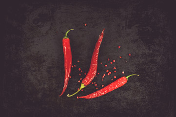 Red chili with peppercorns on black background. Top view, flat lay, moody style