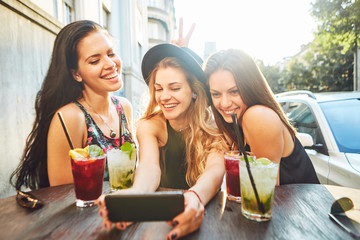 Three young woman at cafe taking selfie