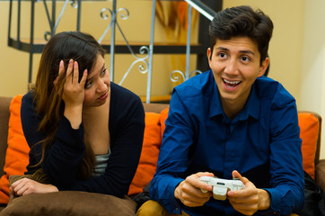 Handsome young man playing video games on the couch while girlfriend is bored, concept about home entertainment, video games