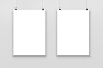 Two Blank paper poster mockup isolated on a gray background.