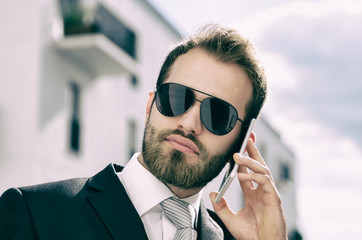 Handsome businessman talking on phone city outdoor