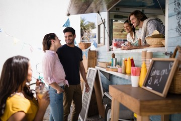 Couple interacting with each other at food truck van