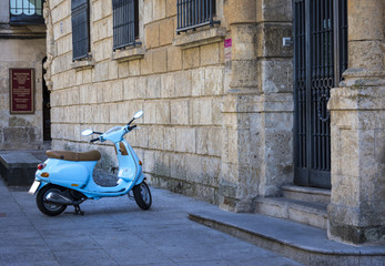 Cian vintage scooter parked on a sidewalk.