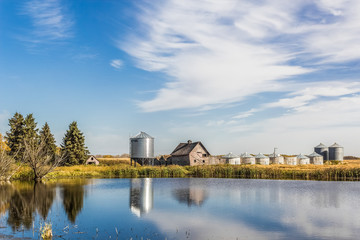 old farm yard with grain bins and a pond in the foreground