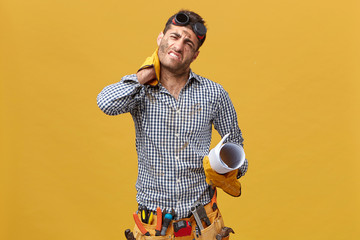 Tired repairman having exhausted look after long and stressful day of work holding his hand on neck having pain there wearing gloves, belt with tools and gloves and holding blueprint isolated