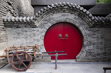 A wooden cart in front of a round door way at the south gate of the xian city wall in Shaanxi province China.