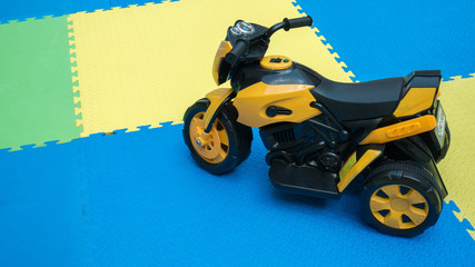 Close up of yellow motorcycle toy on rubber floor with copy space at playground. Cute little motorcycle on safe zone for kids with blank space for text.
