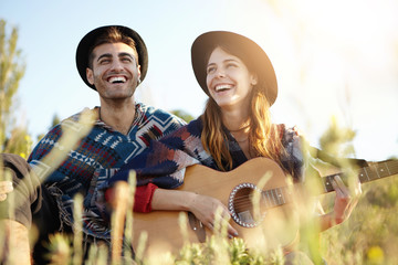 Sensual free two people sitting together at greenland having joy while playing guitar and singing songs. Young family resting at green field enjoying calm atmosphere and beauty of nature having smiles