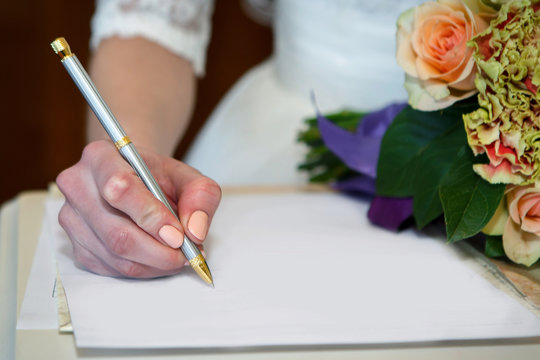 Hand of the bride signing the marriage contract on paper with a pen. Important wedding documents for signature.