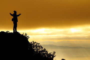 Silhouette of a man on top of mountain