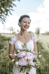 Beautiful bride smiling and holding bouquet