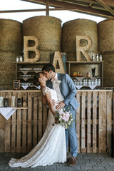 bride and groom kissing in front of the bar