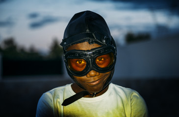 Black child with glasses and aviator cap