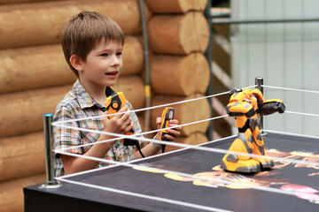 Boy playing battle fighting robot with remote control outdoors