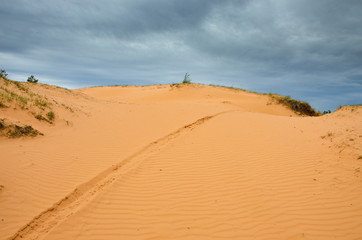 The big sand dune and dark cloudy sky.