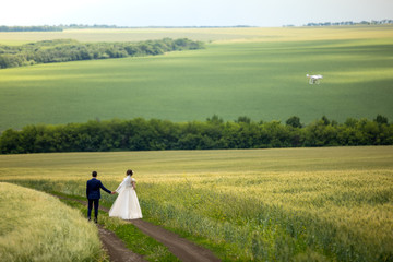 The newlyweds stand on the road in a field of wheat. Next to the bride and groom flies the drone and shoots a video. just married