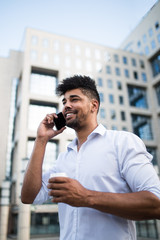 Young handsome Afro American man standing in front of huge modern business building smilling and talking on cell phone.