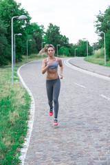 Bellissima ragazza giovane sportiva fa jogging all'aperto in mezzo la natura