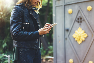 Fotomurales - Girl in leather jacket holding smart phone on background sun atmospheric city, hipster using in female hands and texting mobile, street lifestyle, tourist planing route in summer concept