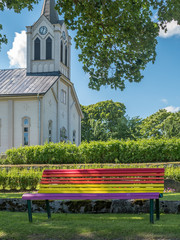 Rainbow flag colors on bench, church in background. Gay marriage concept.