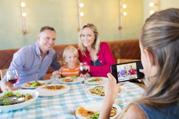 Girl photographing family through mobile phone