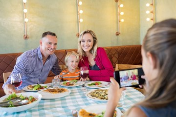 Girl photographing family through smart phone
