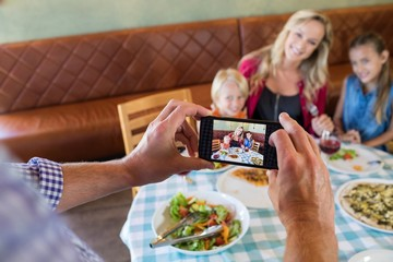 Cropped hand of father photographing family at restaurant