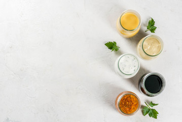 Set of dressings for salad: sauce vinaigrette, mustard, mayonnaise or ranch, balsamic or soy, basil with yogurt. Dark white concrete table. Copy space top view