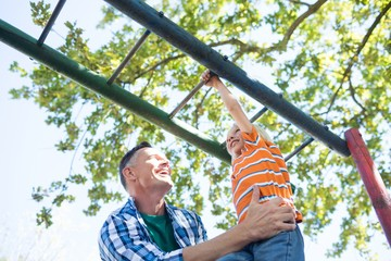 Father holding son playing on jungle gym at playground