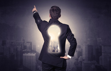 Businessman standing with keyhole on his back