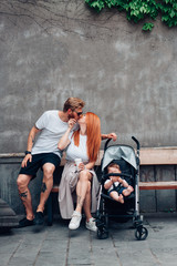 Mom, Dad and little son in a pram