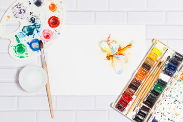 Hand Drawn Sketch of Watercolor Orange Dragonfly,with lying paints, paintbrushes and palette on the white brick background - concept of human creativity,top flat view. Central empty place for text