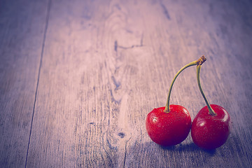 Bright ripe cherry on a gray wooden background.