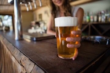 Barmaid holding beer glass